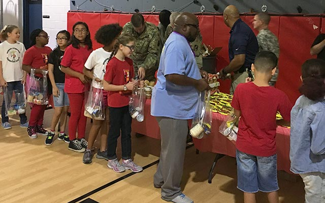Volunteers from CarMax and the military joined General Stanford Elementary School students to stuff weekend meal bags.
