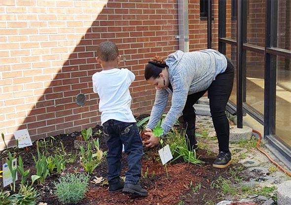 Student and volunteer working in flower garden